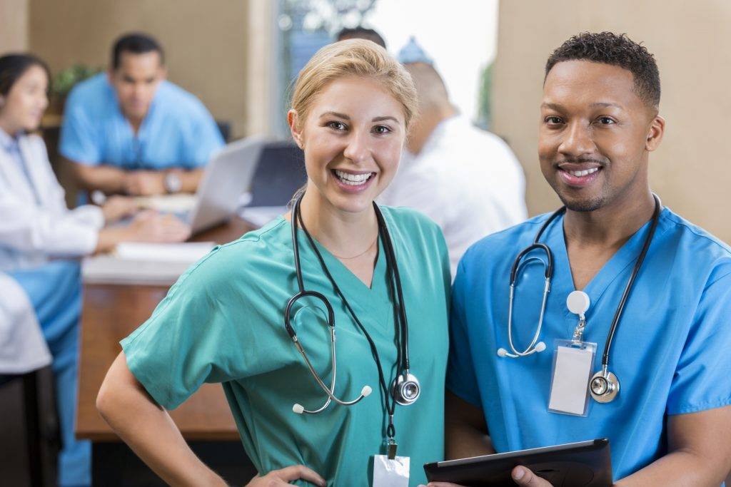 Young Caucasian female and male mid adult African American nurses smile before hospital staff meeting. The woman is wearing green scrubs and the man is wearing blue scrubs. They are both wearing stethoscopes. People are talking in the background.