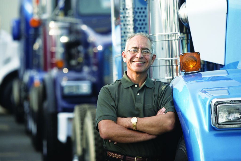 Middle aged man smiling beside his truck