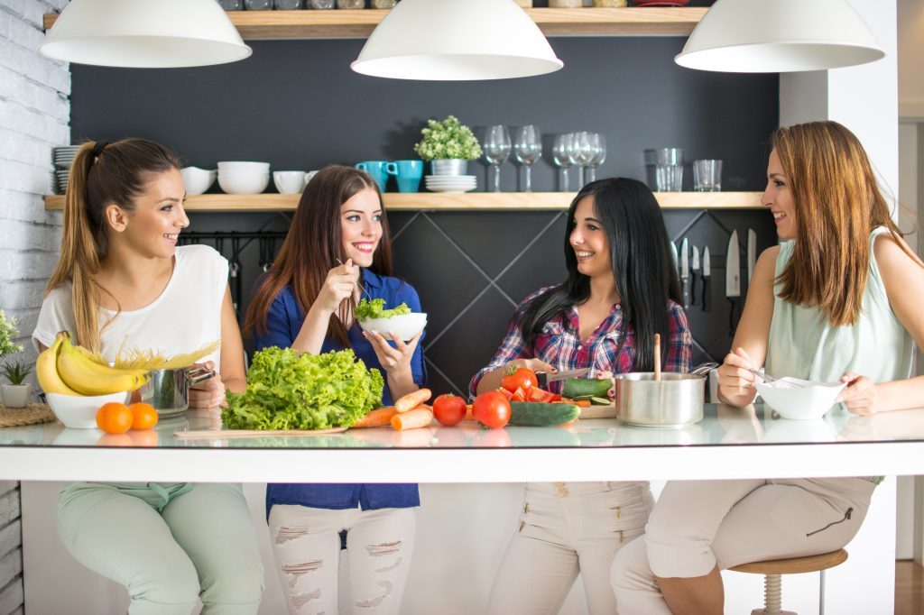 four young women standing behind a table of vegetables