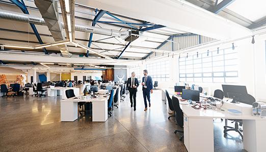 two men walking in an office